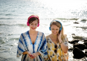 women listening to music on beach