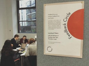 student discussion at table, poster on display