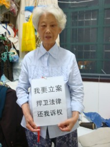 "Mrs He (under house arrest, her home was demolished for the China National Pavilion) holding a statement that reads ""I want my complaint to be lodged by the courtroom. Please defend the law and respect my right to sue."""