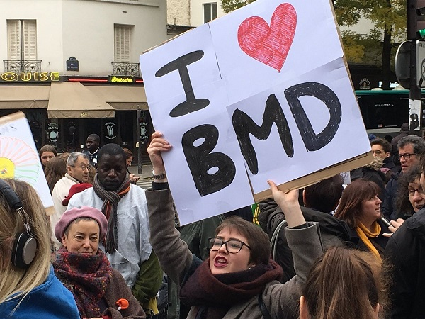 A photo from a demonstration of an activist holding a placard above her head with stating I love BMD.