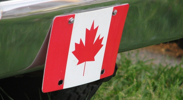 Picture of the bumper of a car with a Canadian flag sign bolted to it.