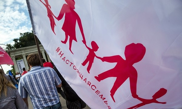 A person pictured from behind carrying a large white flag with an outline of children and adults holding hands and Cyrillic text underneath.