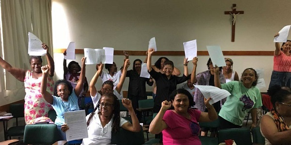 A group of women domestic workers holding up their papers and raising their fists in celebration.