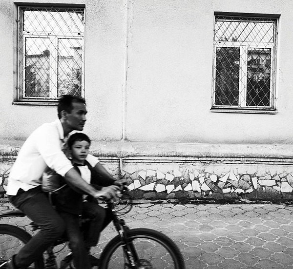 Black and white photo of a man riding a bicycle with a young child sitting in front of him on the crossbar of the bike.