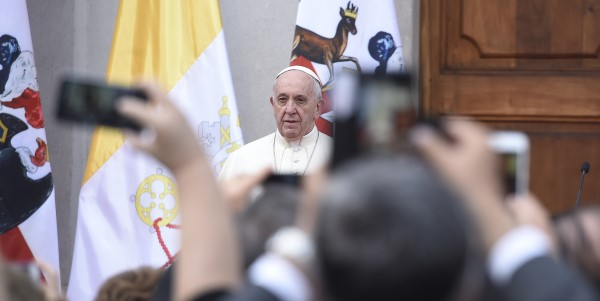 Pope Francis addressing a crowd in focus in the background with raised arms taking pictures of him in the foreground