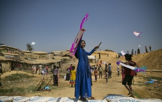 A woman dressed in blue holding up a kite in the centre foreground, taken on International Women's Day at a Rohingya refugee camp in Bangladesh