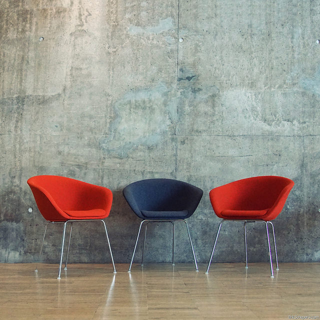 Image of three chairs; two red with one dark grey in the middle