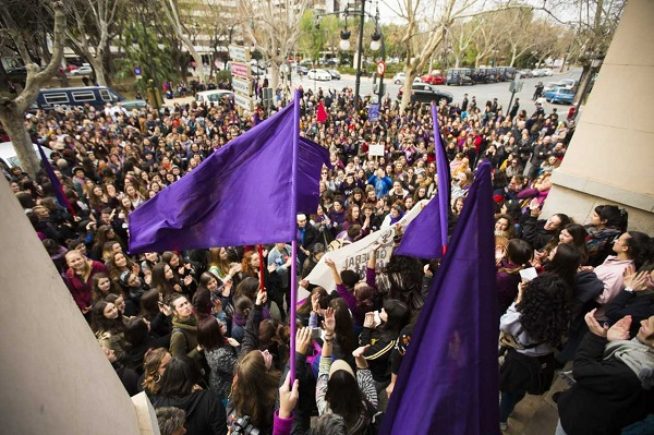 Picture of a crowd, some extending three purple flags above the heads in the foreground
