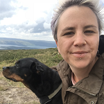 Image of author, with a dog, and a landscape in the background