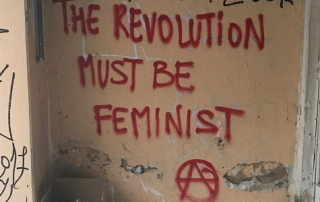 "Graffiti in red on a wall: ""The revolution must be feminist"" and anarchist A sign"