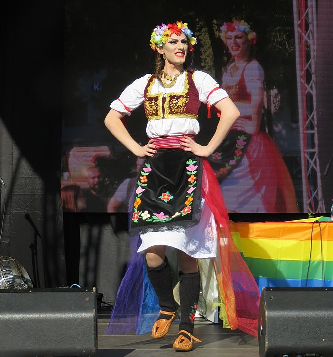 Drag queen dancing on a stage with hands on hips, with pride flag in the background