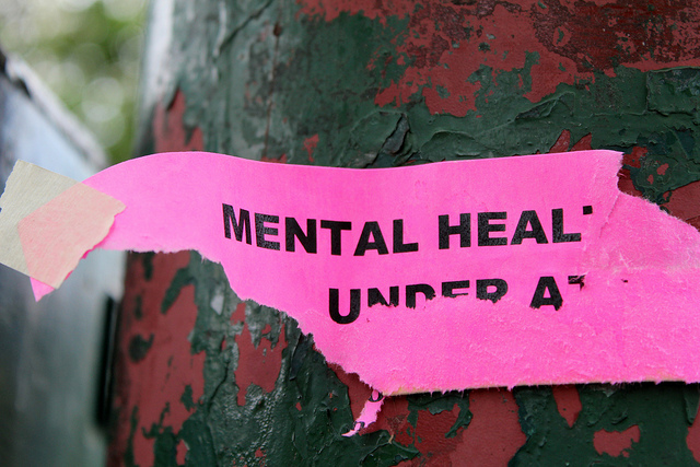 close up of a torn piece of pink paper with words mental heal visible and some partial text on the next line torn which suggests the full message had been 'mental health under attack'