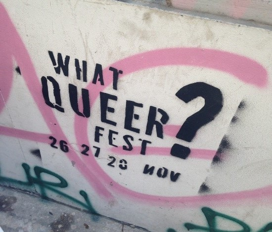 the text 'what queer fest?' sprayed in black on a concrete wall in black along with pink and green graffiti