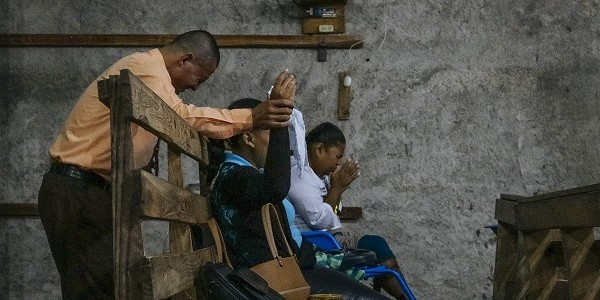 People praying on a wooden bench