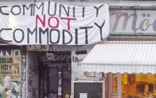 "A shop front with home-made banner above with text ""Community not commodity"""