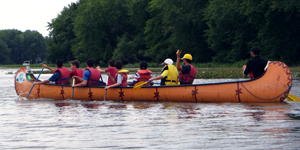 Volunteers oversee kids paddling a Rabaska as part of a day camp in Montreal (credit: Zena Xing)