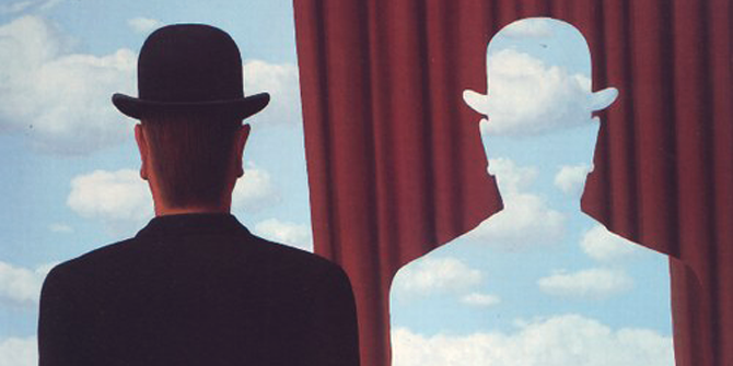 An abstract painting showing the silhouette of a man and the same outline cut into a stage curtain next to him.