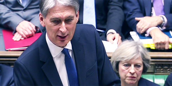 Philip Hammond delivers the 2016 Autumn Statement as Theresa May looks on from the benches.