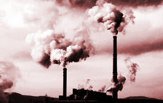 A black and white silhouette of power station chimneys belching out smoke