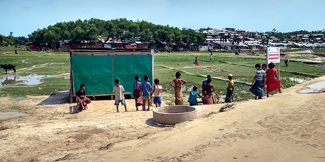 Children playing by the side of a road in a Rohingya refugee camp