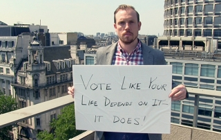 "Brian Klaas holding a placard which says, ""Vote like your life depends on it - it does!"""