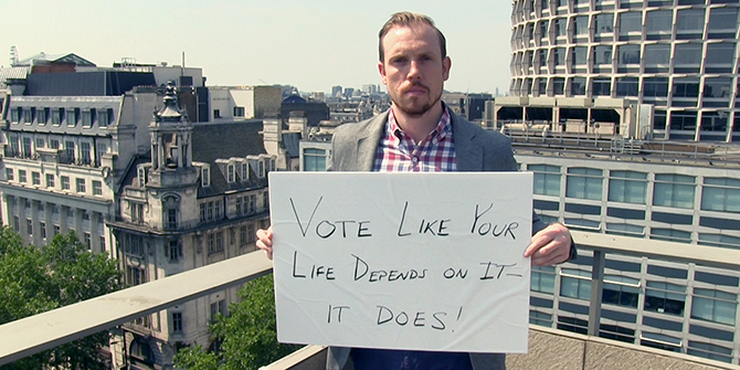 """Brian Klaas holding a placard which says, """"Vote like your life depends on it - it does!"""""""