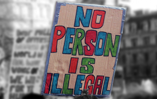 A close up of a sign at a protest which reads, 'no person is illegal'. The sign is in colour whilst the background is black and white.