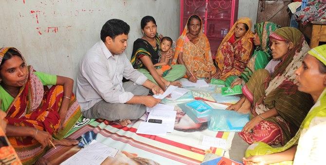 BRAC staff talking with CFPR-TUP member in a meeting in Sampur slum, Sutrapur, Dhaka.