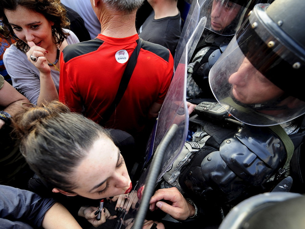 Skopje, a woman uses a police shield as a mirror in the midst of violent protests. This photo was widely shared on social media - see: http://i100.independent.co.uk/