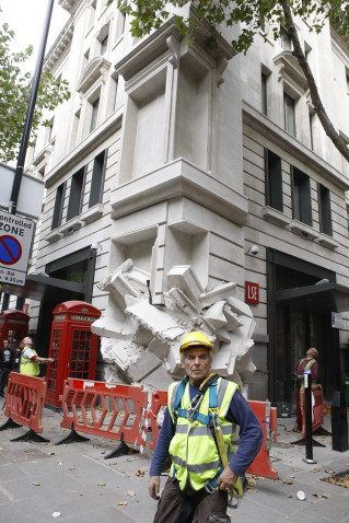 A workman poses in front of the 5-storey sculpture 'Square the Block' by Richard Wilson RA on the northwest exterior of the LSE New Academic Building on Kingsway. 14th September 2009