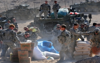 U.S. Soldiers with Charlie Company, 1st Battalion, 17th Regiment unload Humanitarian aid for distribution to the town of Rajan Kala, Afghanistan Dec. 05, 2009. Charlie Company used their Stryker armored vehicles to move the Humanitarian aid from the Joint District Community Center to the town of Rajan Kala. (U.S. Air Force photo by Tech. Sgt. Francisco V. Govea II/Released)
