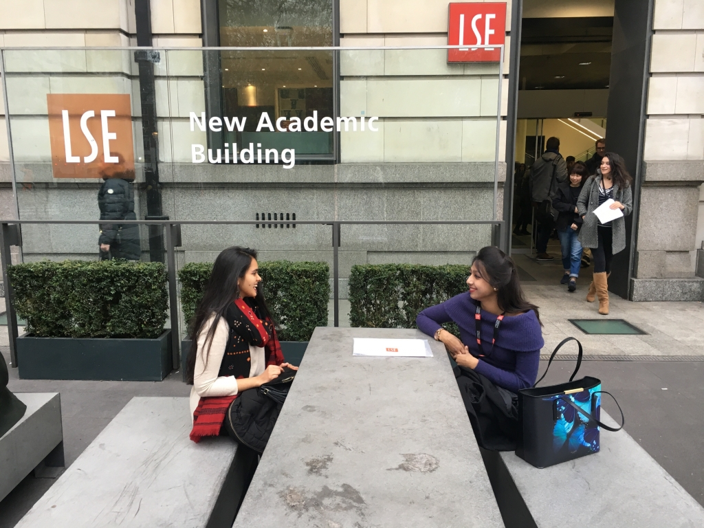 Two people standing outside building