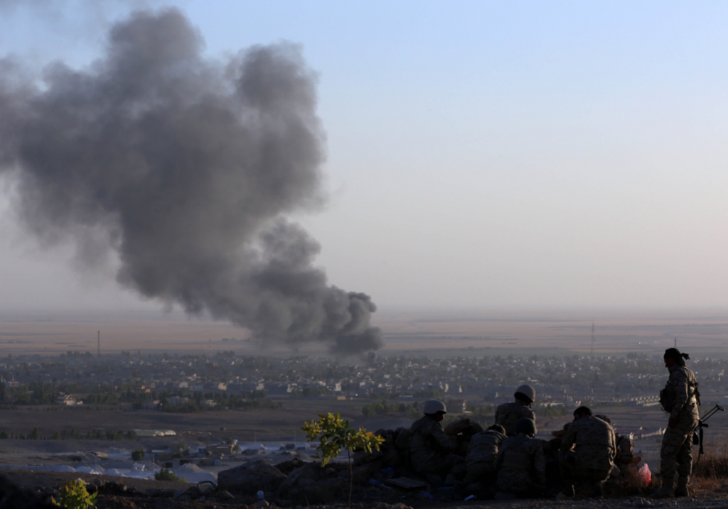Iraqi Kurdish Peshmerga fighters look on as smoke billows from the town Makhmur, about 175 miles north of the capital Baghdad, during clashes with Isis militants. AFP/Getty Images
