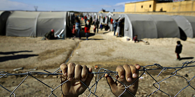 A refugee from the Syrian town of Kobani holds onto a fence that surrounds a refugee camp in the border town of Suruc, Turkey.  Copyright Jordi Bernabeu Farrús, flickr.com