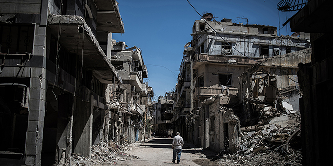 A Syrian man walks among severely damaged buildings in downtown Homs, Syria, 2014. (Xinhua/Pan Chaoyue)