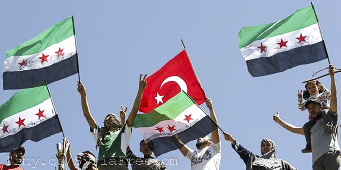 Syrian refugees wave Turkish and Syrian Independence flags during a protest against Assad at Yayladagi refugee camp.