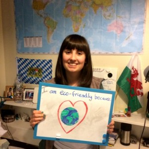 """Student holding a whiteboard saying """"I'm eco friendly because I love the world"""""""
