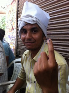 Young man showing his ink-marked finger after voting, May 12 2014