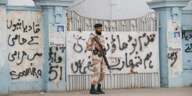 Armed security guard outside gated house in Karachi. Image credit: flickr/Benny Lin CC BY-NC 2.0